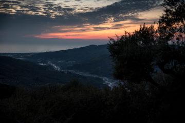 Sonnenuntergang über Flusslauf und grüner Hügellandschaft