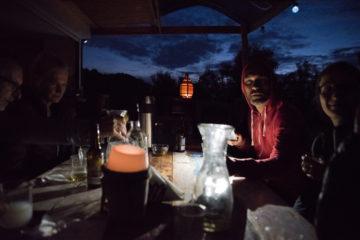 Gruppe am Abend sitzt an gedecktem Tisch