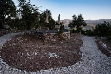 """Erhöhte Terrasse auf Steinhügel, Steinsonne und Schriftzug """"Live"""" aus Stein"""