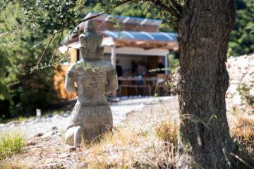 Kniender Buddha als Rückenansicht