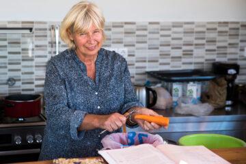 Frau schält Karotten und lächelt dabei