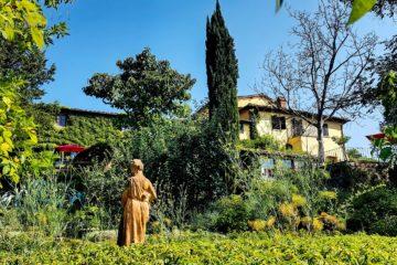 Haus erhöht mit grüner Efeu-Fassade und Statue