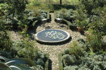 Kleiner Teich mit Seerosen und Stühlen in Garten