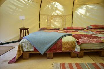 Nahaufnahme Futons im Zelt mit roter Quiltdecke