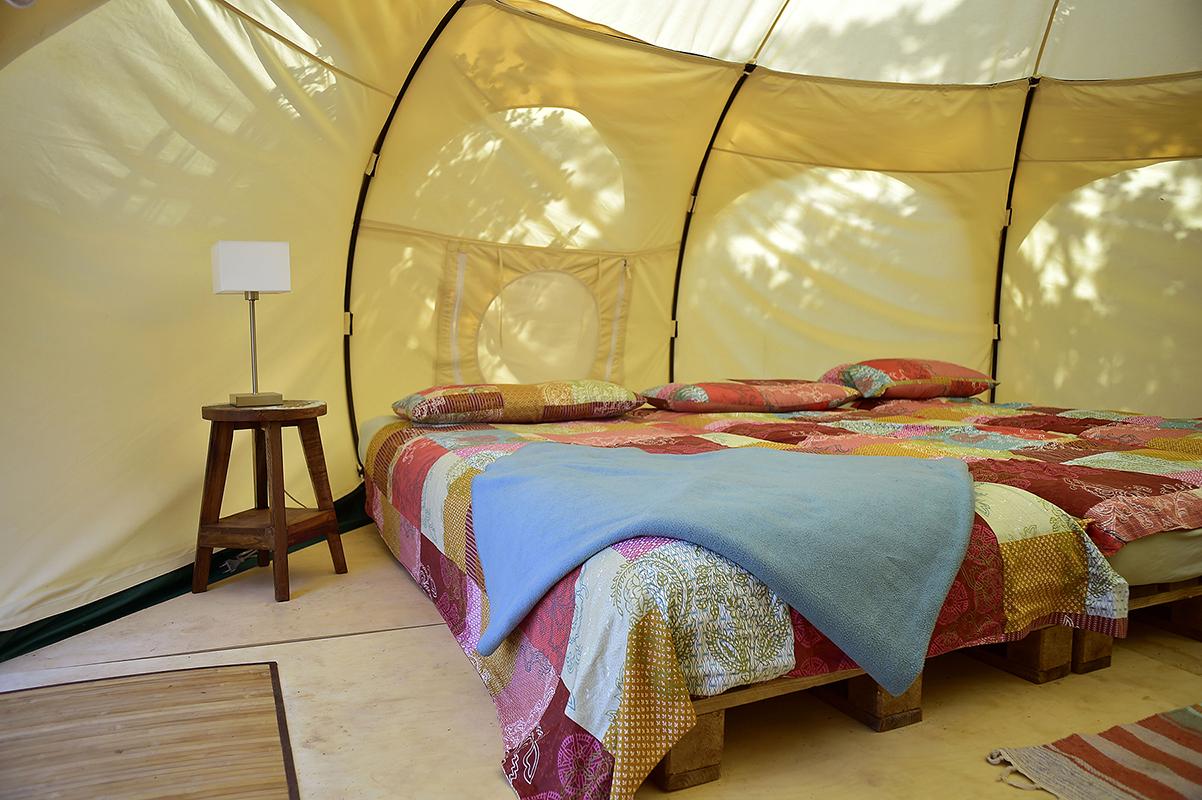 Zelt mit zwei Futonbetten und bunte Tagesdecke in Quilt-Optik