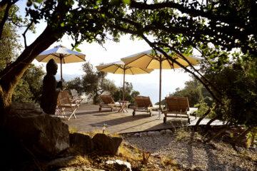 Holzterrasse mit Sonnenschirmen und Buddha-Statue