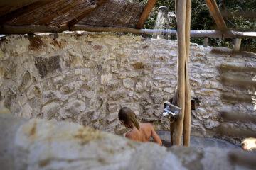 Frau duscht in Open Air Dusche