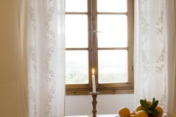 Fesnter mit weißen Spitzenvorhängen vor Holztisch mit brennender Kerze