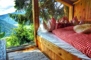 Koje im Baumhaus mit rot-weiß-karierter Bettwäsche und Panoramafebster