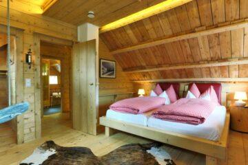 Doppelbett mit rot-weiß-karierter Bettwäsche unter dem Dach