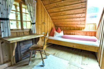 Bett und schmaler Schreibtisch unter dem Dach