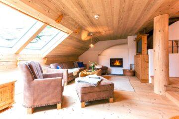 Couchlandschaft unter Dachschräge mit großem Ofen