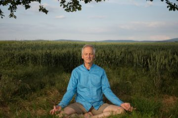 Mann meditiert auf Wiese im Lotussitz