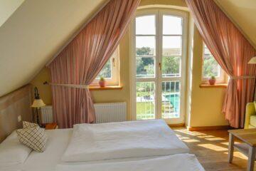 Bett am Giebel mit drei Fenstern und Blick nach draußen