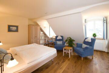 Zimmer mit Doppelbett und blauen Sesseln