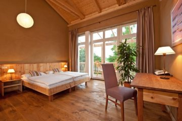 Zimmer in hellem Holz, Doppelbett und Balkon