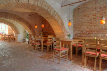 Gewölbe mit Stühlen und Tischen