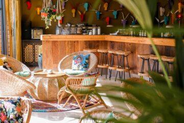 Lounge-Bereich mit Rattanmöbeln an Holztheke und bunten Gypsy-Kissen mit Frauenportraits