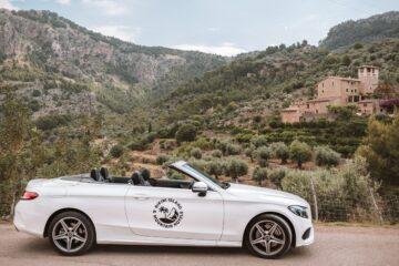weißes Cabrio mit mallorcinischer Landschaft