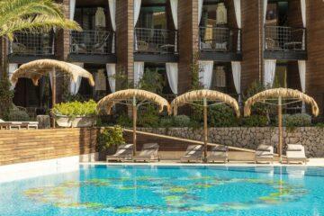 Pool mit Palm-Sonnenschirmen und kleinen Balkonen am Hauptgebäude