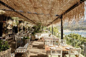 Palmgedeckte Terrasse bestuhlt mit Blick auf die Bucht