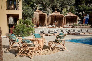 Sitzgruppe mit türkisen Kissen am Pool