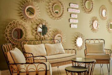 Hellgrüne Wand mit verschiedenen Rattanspiegeln und Couch-Garnitur