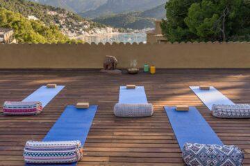 Terrasse mit Yogamatten, Steinelefant, goldener Räucherschale mit Blick auf die Bucht