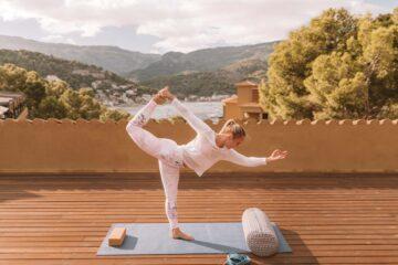 Frau macht Yoga-Pose auf Terrasse
