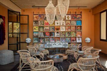 orangener Aufenthaltsraum mit bunter Schallplattenwand und Rattanstühlen