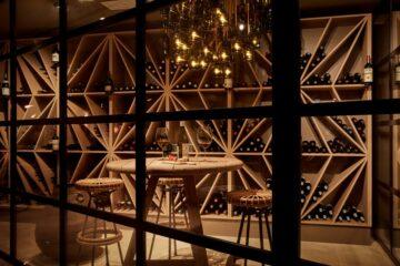 Regal mit Weinen und Tisch mit zwei Rattan-Barhockern