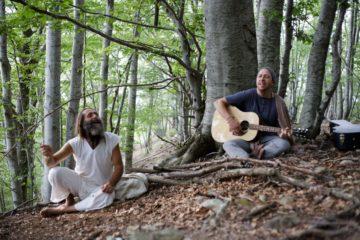 Zwei Männer singen mit Gitarre unter den Bäumen