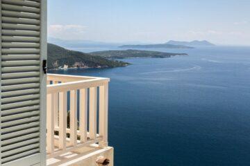Terrasse mit Bänken und Stühlen über dem Meer