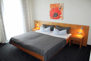 Doppelbett mit graier Bettwäsche und gemaltem Mohnbild an der Wand