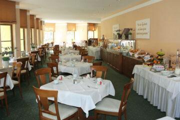 Tische mit Holzstühlen und Frühstücksbuffet entlang der rechten Wand