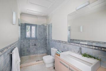 Badezimmer mit Dusche und grauen KAcheln