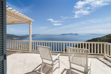 Terasse mit zwei weißen Stühlen über blauem Meer