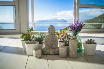 Buddha und Pflanzgefäße vor Fenster mit Aussicht aufs Meer