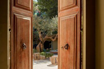 Holztüre die sich in Innenhof mit Olivenbaum öffnet