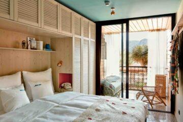 Zimmer mit Balkon und weißer Holzfront