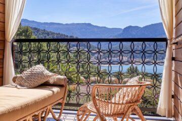 Balkon mit Sessel und Chaise Lounge und Blick über die Bucht