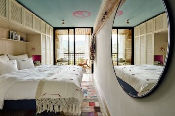 Schlafzimmer mit großem rundem Spiegel an rechter wand