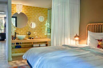 Bett mit gelb-gefliester Waschecke und Zugang zum Wohnraum und Terrasse