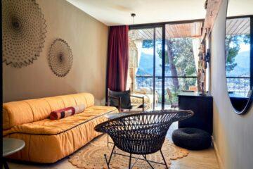 Wohnraum mit gelbem Sofa und schwarzem Rattanstuhl