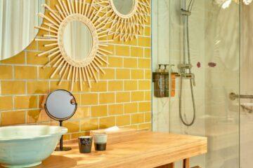 Mit gelben Kacheln gefliestes Bad und Dusche