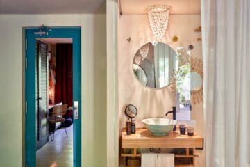 Waschraum mit blauer Tür und Spiegel der Schreibtisch zeigt