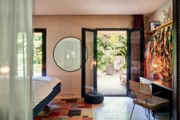 Zimmer mit Tür die sich auf große Terrasse inmitten von Palmen öffnet
