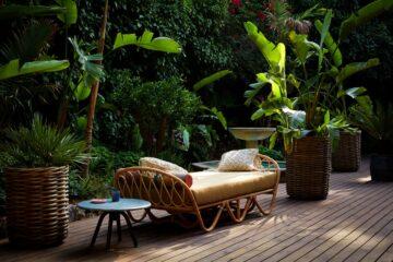 Tagbett auf Terrasse neben Brunnen inmitten von Bananenpalmen
