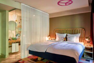 Bett mit abgetrenntem Waschraum und pinkem Peace-Zeichen an Decke
