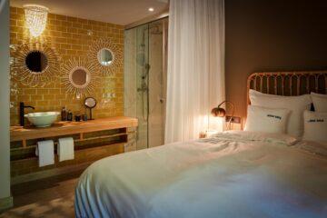 Bett mit beleuchteter Waschecke und gelb gefliester Wand mit Spiegeln